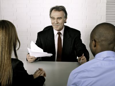 Manager issuing a disciplinary warning form to two employees.