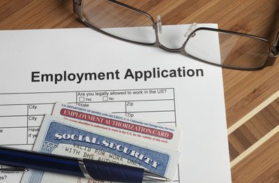 a job application with a pen and social security card resting on it