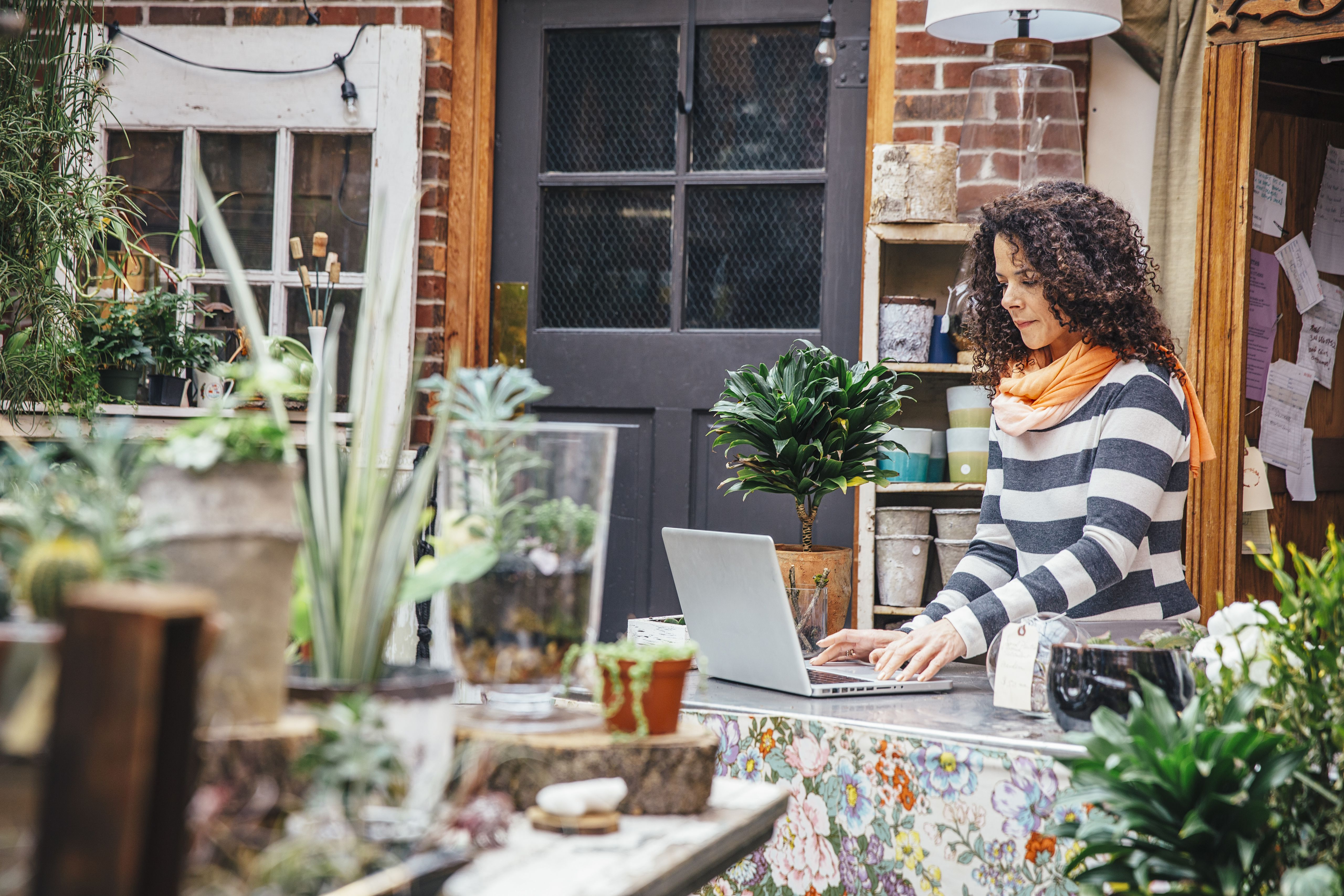 woman with plants on computer