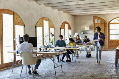 Casual workplace with workers at tables and working in groups