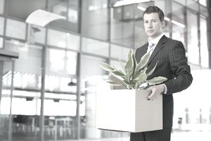 Portrait of a serious looking business executive carrying a cardboard box