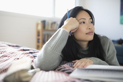 Pensive woman with pencil journaling, looking away on bed