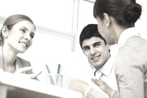 Woman reviewing a sales offer letter with two colleagues.