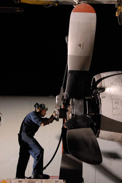 a sailor installing a propeller on the number two engine of a P-3C Orion aircraft