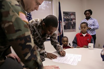 Military officer with a recruit signing enlistment paperwork